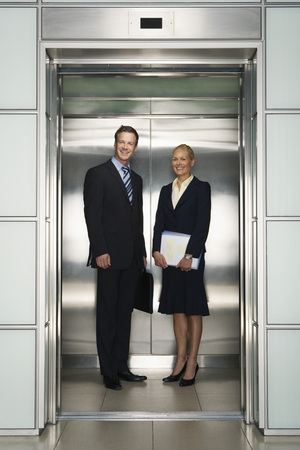 late 30s: Smiling Businessman and Businesswoman in Office Elevator