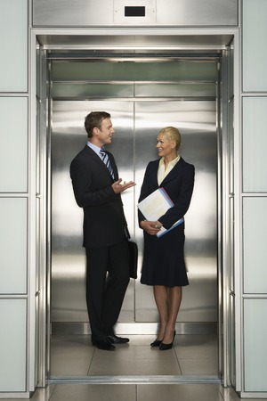 late 30s: Businesspeople Talking in Elevator