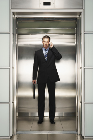 early thirties: Businessman Using Cell Phone on Elevator LANG_EVOIMAGES