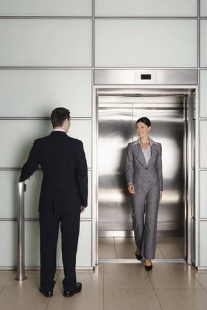 late 30s: Businesspeople Using Office Elevator LANG_EVOIMAGES