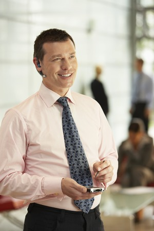 late 30s: Businessman Using Wireless Headset and PDA