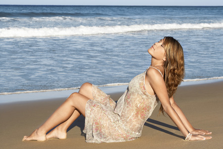 holidaying: Young Woman Relaxing on Beach LANG_EVOIMAGES