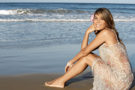 holidaying: Pretty Young Woman Sitting on Beach