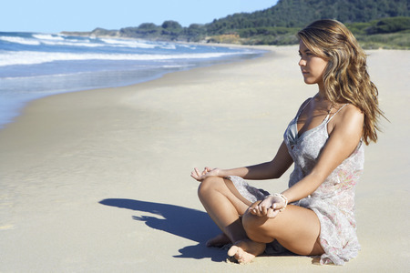 early twenties: Young Woman Meditating on Beach LANG_EVOIMAGES