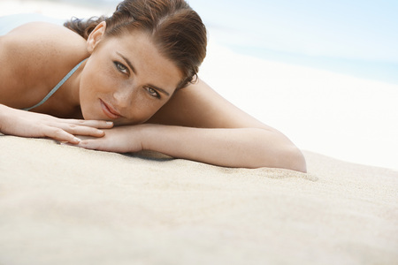 holidaying: Pretty Young Woman Lying on Beach