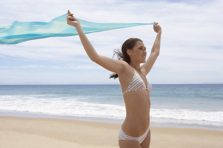arms lifted up: Carefree Young Woman on Beach LANG_EVOIMAGES