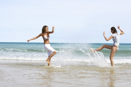 holidaying: Two Young Women Splashing Each Other at Beach