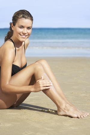 holidaying: Young Woman at Beach Putting Lotion on Legs LANG_EVOIMAGES