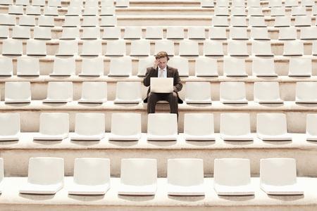 fortysomething: Businessman Using Laptop in Auditorium