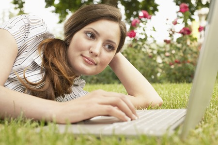 Young Woman Using Her Laptop in the Grass Stock Photo