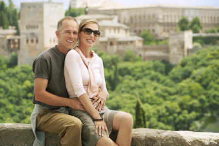 Tourist Couple Relaxing on Wall Stock Photo