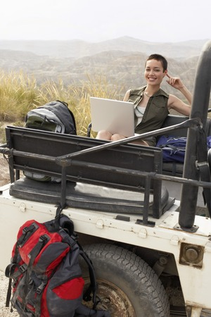 holidaying: Hiker Using Laptop in Land Rover
