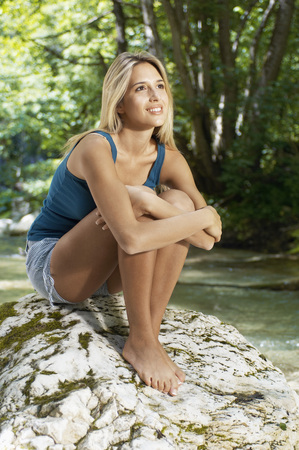 Young woman sitting by river in forest