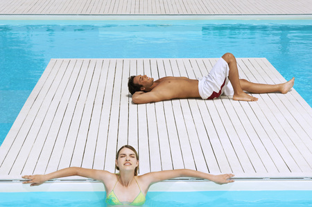 early twenties: Couple Relaxing at Swimming Pool
