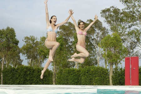 zealous: Young Women Jumping into Swimming Pool
