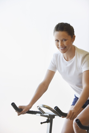 early thirties: Woman on Exercise Bike LANG_EVOIMAGES