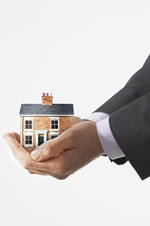 hand holding house: Person holding small house in cupped hands