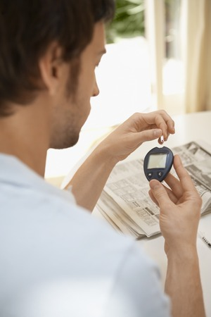 early thirties: Man Using Blood Sugar Meter