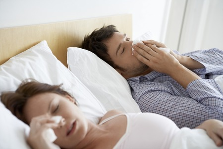 maladies: Couple with Colds Lying in Bed