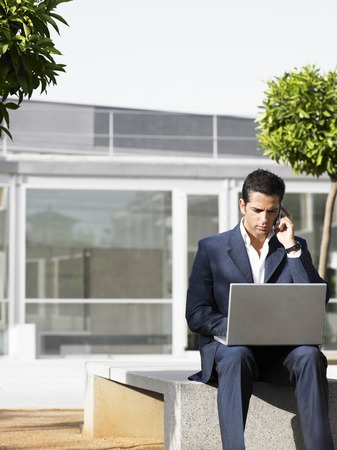 kw: Businessman Using Laptop and Cell Phone LANG_EVOIMAGES