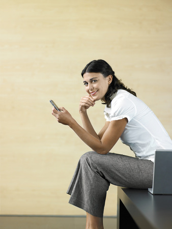 woman dialing phone number: Office Worker Using Cell Phone LANG_EVOIMAGES