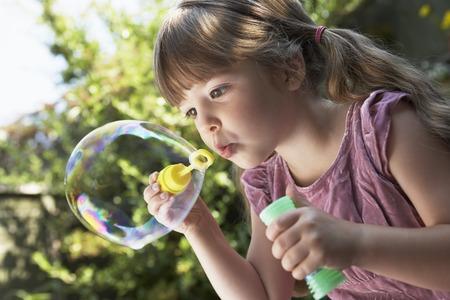 Girl Blowing Soap Bubbles LANG_EVOIMAGES