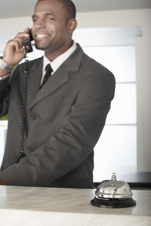 front desk: Businessman on Phone at Hotel Reception Desk LANG_EVOIMAGES