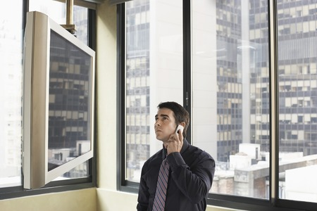 Businessman Using Cell Phone and Watching TV Stock Photo - 5494515