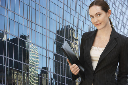 beforehand: Businesswoman by Office Building Holding Daily Planner LANG_EVOIMAGES