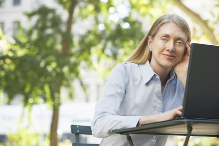 Woman Daydreaming Outdoors at Table with Laptop Stock Photo - 5494529