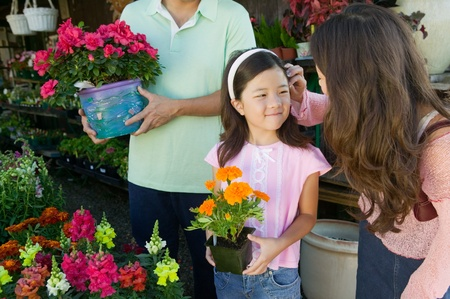 plant nursery: Mother fixing hair of daughter in plant nursery
