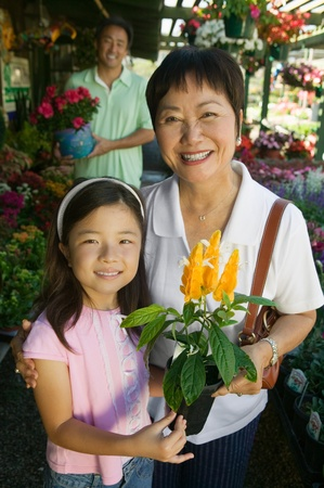 two people with others: Grandmother and granddaughter in plant nursery holding flowers portrait