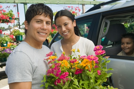 two people with others: Couple Loading Plants into Minivan at plant nursery portrait