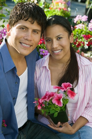 Couple Sitting Among flowers at plant nursery portrait Stock Photo - 8822566