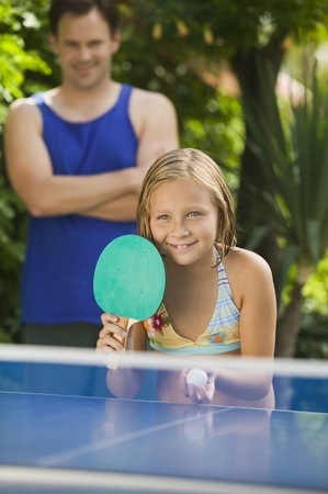 Girl (7-9) playing table tennis with father in background. Stock Photo - 8822589