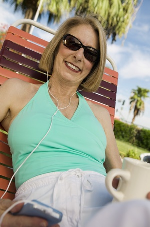 halterneck: Woman lying on sunlounger listening to portable music player portrait. LANG_EVOIMAGES