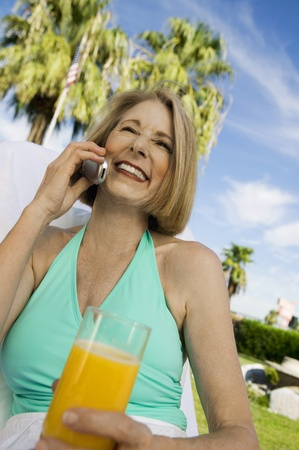 halterneck: Woman holding glass of juice using mobile phone outdoors.
