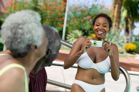 african bikini: Woman wearing bikini photographing senior couple outdoors.