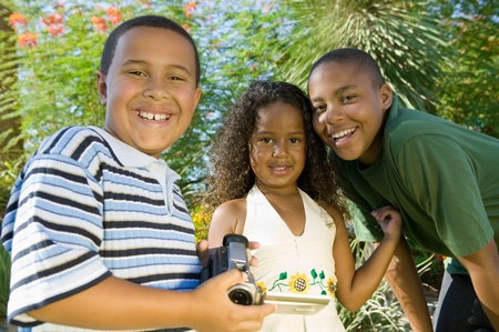 pre teen boy: Boy (7-9) holding camcorder with younger sister (5-6) and older brother (10-12) portrait.