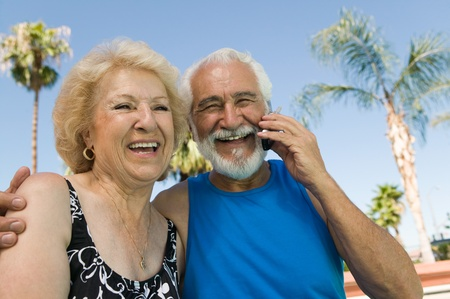 Senior Couple sitting outdoors man using mobile phone portrait. Stock Photo - 8822618