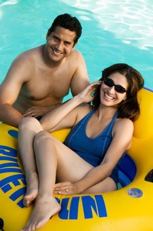 swimming pool woman: Couple in swimming pool woman lying on inflatable raft elevated view portrait.