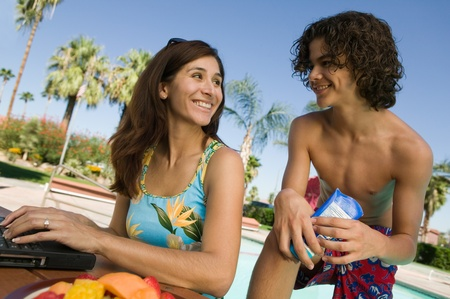 Mother and son (13-15) at swimming pool mother using laptop. Stock Photo - 8822639