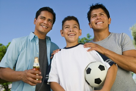 Boy (13-15) holding soccer ball with two brothers outdoors front low angle view. Stock Photo - 8822644