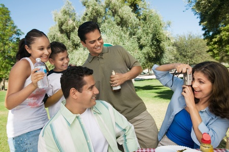 Woman using digital camera photographing son (13-15) with father brother and sister. Stock Photo - 8822653