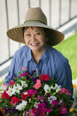 Woman holding flowers in garden (portrait) Stock Photo - 8822680