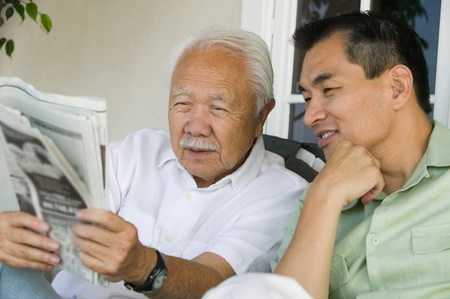 Father and son reading newspaper outdoors Stock Photo - 8822682