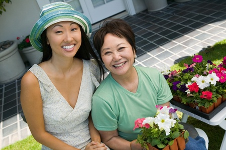 asian gardening: Mother and daughter with flowers smiling (portrait)