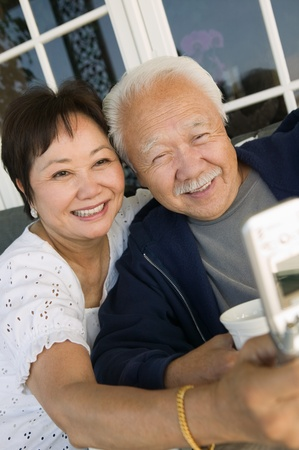 Couple using mobile phone outdoors Stock Photo - 8822701