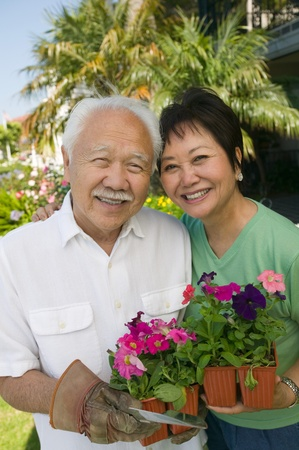 60s adult: Senior couple holding flowers outdoors (portrait)