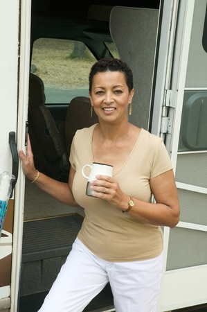 Woman with drink beside motor home (portrait) Stock Photo - 8822713